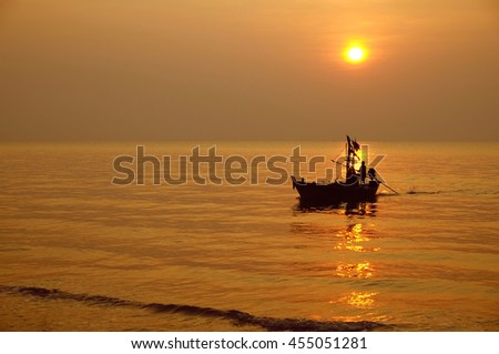 sunset fantasy with silhouetted boat along its journey against a vivid colorful sunset.