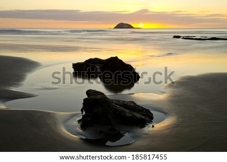 Sunset from Maori Bay in Muriwai, New Zealand - stock photo