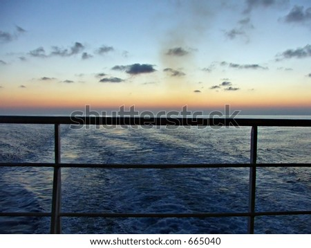 sunset from the back of a boat - stock photo