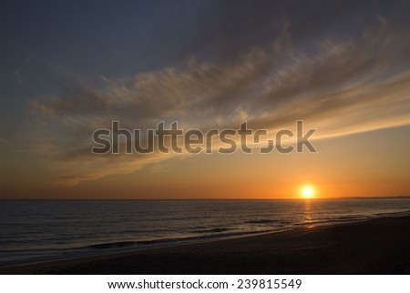 Sunset from the beach at Praia de Faro, Algarve, Portugal. - stock photo