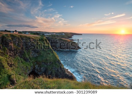 Sunset from the cliffs at Port Gaverne on the rugged north Cornwall coast - stock photo