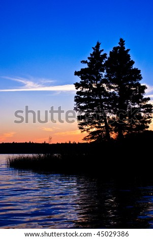 Sunset glow beyond a northern Canadian lake at twilight with the silhouette of trees in the foreground. - stock photo