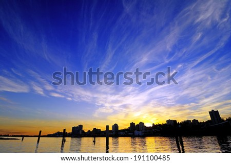 sunset glow with silhouette of a city by a river