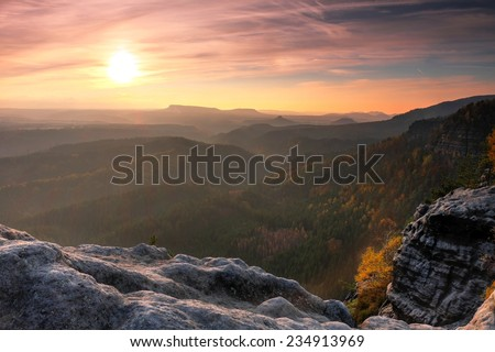 Sunset in a beautiful rocky park Bohemian-Saxony Switzerland. Sandstone peaks and hills increased from foggy background, the fog is orange due to sun rays.  - stock photo