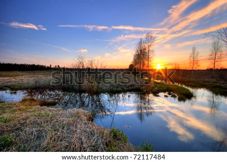 Sunset in a meadow in early spring - stock photo