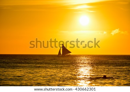 Sunset in Boracay, Philippines with a person that swim in foreground