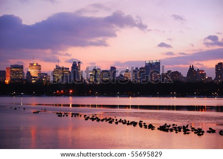 Sunset in Central Park New York City with skyline and ducks in lake - stock photo