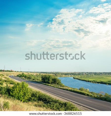 sunset in clouds over river and asphalt road - stock photo