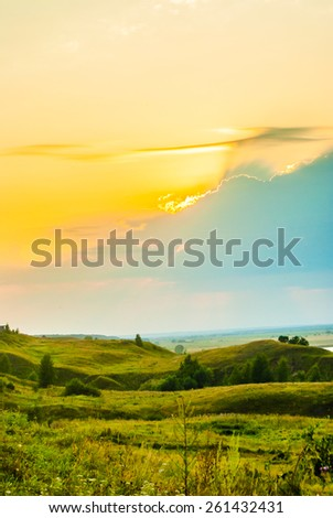 Sunset in countryside. Colorful landscape with trees, hills, rever and cloudscape - stock photo