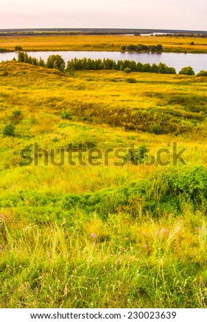 Sunset in countryside. Colorful landscape with trees, hills, river - stock photo