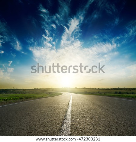 sunset in deep blue sky over road