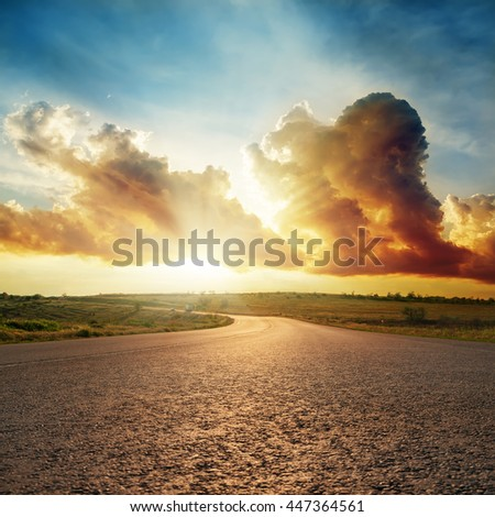 sunset in dramatic clouds over asphalt road - stock photo