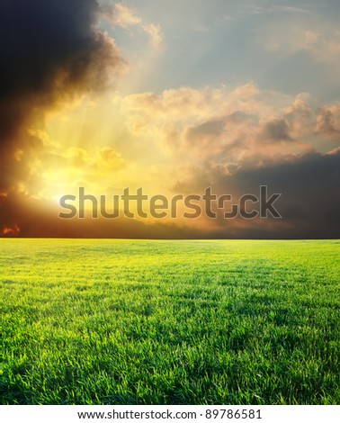 sunset in dramatic sky over green field - stock photo