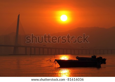 Sunset in Hong Kong along the coast, with some boats showing the fishing village atmosphere. - stock photo