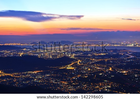 Sunset in Hong Kong plain area over mountains - stock photo