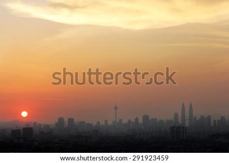 Sunset in Kuala Lumpur with the silhouette of the Kuala Lumpur city skyline - stock photo