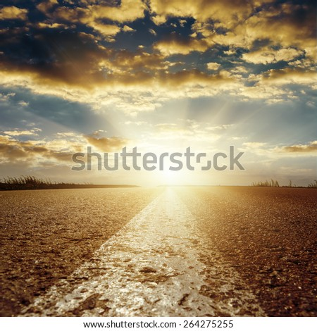 sunset in low clouds over asphalt road with central white line - stock photo