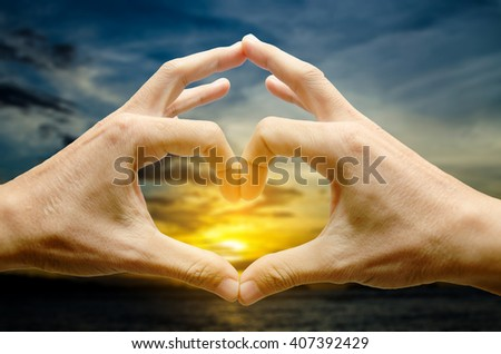 sunset in Man hands shaping a heart symbol on white background - stock photo