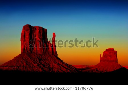 sunset in Monument Valley with both of the Mitten Monuments showing against the sky - stock photo