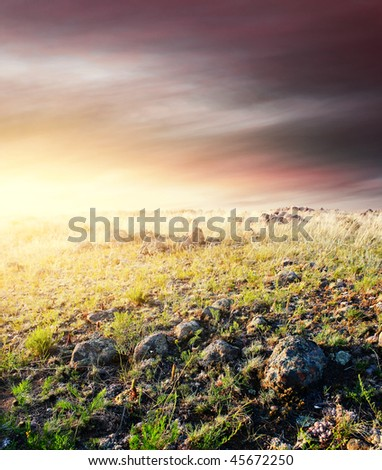 Sunset in mountains with rocky land - stock photo