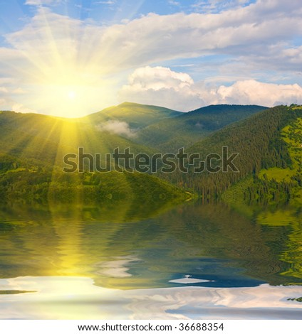 sunset in mountains with water reflection