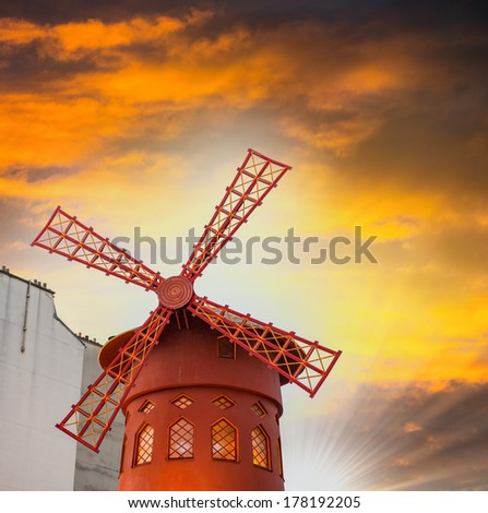 Sunset in Paris. Famous Moulin Rouge red mill. - stock photo