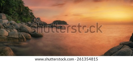 Sunset in phuket beach with rock, island and coconut in Thailand - stock photo