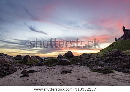 Sunset in Salvador seen from the beach next to the walls of the da Barra lighthouse - stock photo