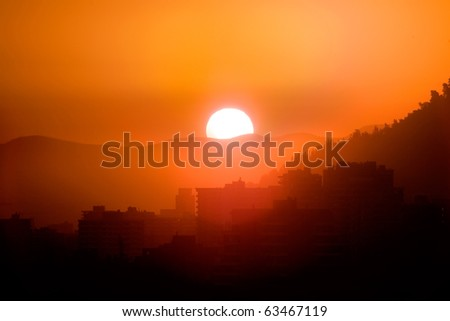 Sunset in Santiago de Chile, with buildings of Las Condes district in the foreground - stock photo
