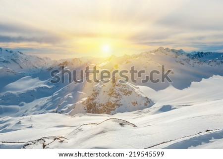 Sunset in snowy blue mountains with clouds. Winter ski resort