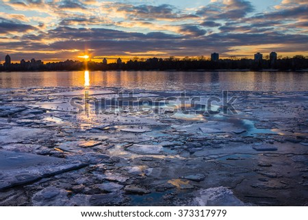 Sunset in the city on the bank of the river; large pieces of ice floating on the water surface