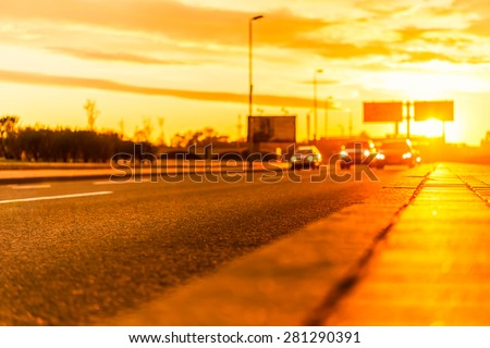 Sunset in the city. View of the flow of cars racing down the highway from the level of the pavement, image in the orange toning - stock photo