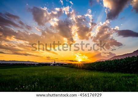 Sunset in the countryside - dramatic sky with clouds, green meadow and cornfield, houses with church, and mountains on background - stock photo