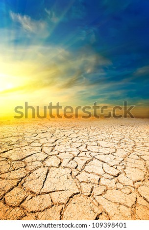 Sunset in the desert against the ground with cracks