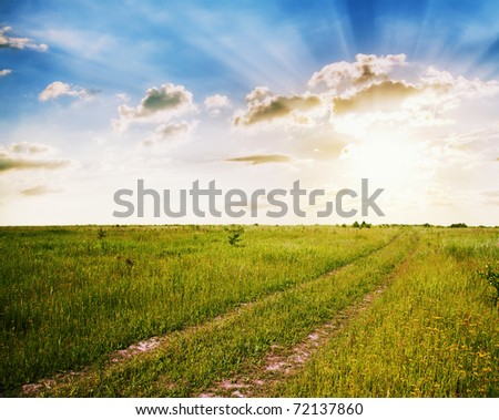 sunset in the fields, rural landscape with country road - stock photo