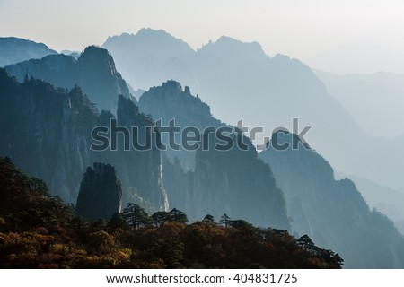 Sunset in the Huangshan Mountain Range - Anhui Province, China. Evening sun lights the cliffs below and observation deck. Mountain range dissolves in the layers of atmosphere. - stock photo
