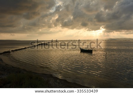 Sunset in the lagoon, where fishermen return to the approach of the impending storm. Dawning. Mediterranean islands. / Fishermen Boat Sunset Lagoon - stock photo