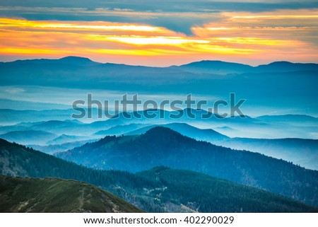 Sunset in the mountains. Dramatic colorful clouds over blue hills - stock photo