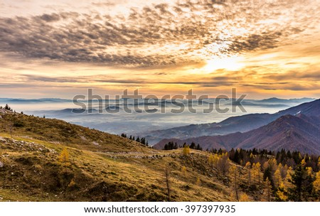 Sunset in the mountains. View of the valley. Golden hour yellow dusk or dawn with sun sunset or sunrise. Europe - Slovenia. - stock photo