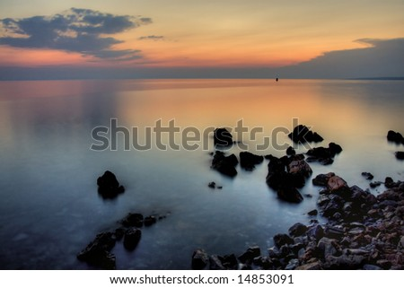 Sunset in the rocky beach in Adriatic Sea - stock photo
