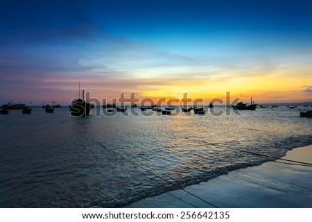 sunset in the sea fishing port and the silhouettes of the boats (Thailand) - stock photo