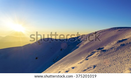 Sunset in the winter snowy mountains. Direct sunlight. Sun beam. Light reflected from the snow. Clear blue sky. Deep shadows - stock photo