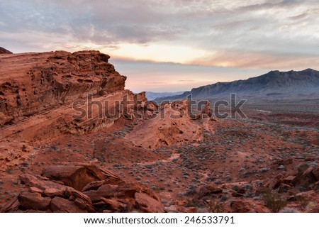sunset in Valley of Fire state park in Nevada with glowing red sandstone and bright color in the clouds - stock photo