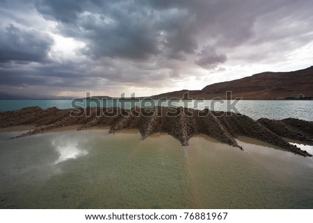 Sunset. Incredible lighting effects on the Dead Sea in Israel. Picturesque sediment mixture of sea salt and mud on the beach - stock photo