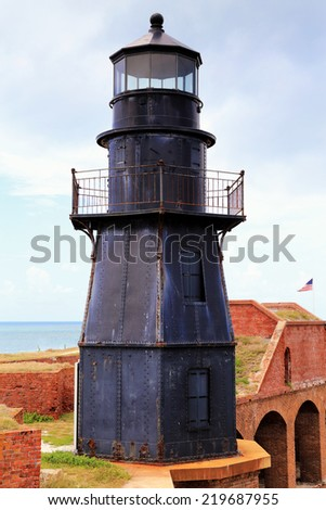 Sunset Key Lighthouse perches atop Fort Jefferson's imposing walls in Dry Tortugas National Park, Florida. - stock photo