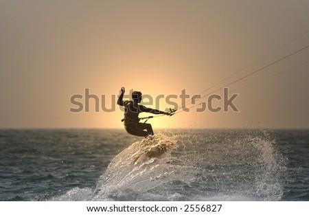 sunset kitesurfer flying over a wave - stock photo