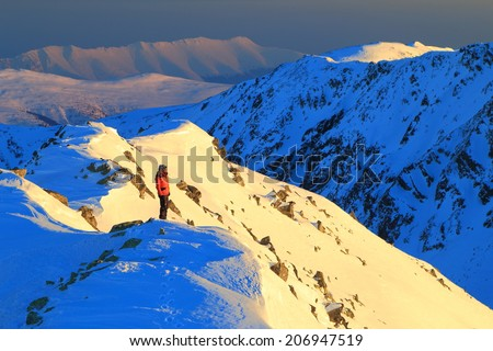 Sunset landscape on the mountains with remote climber standing on snowy summit - stock photo