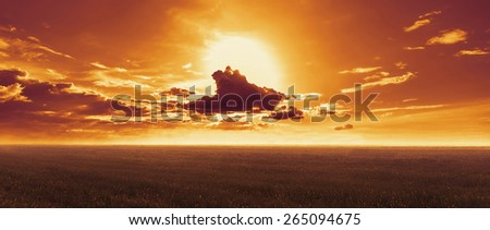 Sunset landscape. Sun sets behind clouds in the evening over meadow in summer - stock photo