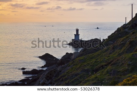 Sunset landscape with a lighthouse in the sea - stock photo