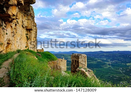 Sunset landscape with big overhung rock and mountain view. Ares in Spain.